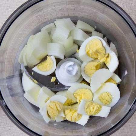 1. Этап. Отварные яйца очистите от скорлупы, нарежьте яйца и лук произвольно. Сложите в чашу блендера и измельчите до однородности.