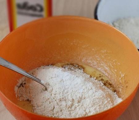 1. Этап. Всыпьте соду и добавьте половину муки. Хорошо вымешайте.