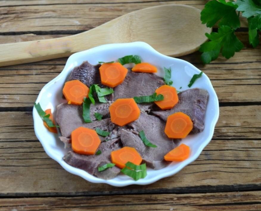 1. Этап. Язык красиво выложите на тарелку средней глубины, украсьте отварной морковью и зеленью.