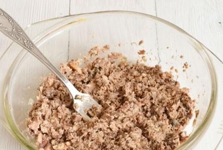1. Этап. Из консервы слейте жидкость, переложите рыбу в глубокую миску и разомните вилкой.