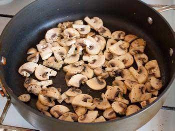1. Этап. Нарезаем тонкими пластинками шампиньоны. В сковороде разогреваем 2 ст. л. растительного масла, кладем грибы, добавляем майоран и жарим, помешивая, около 5 минут.Перекладываем грибы на тарелку.