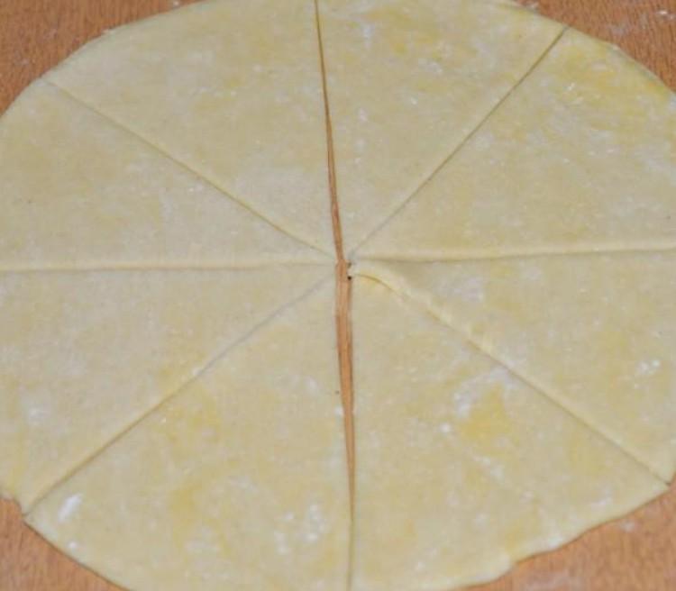 1. Этап. Раскатать на присыпанной поверхности тесто в прямоугольник и нарезать его на треугольники.