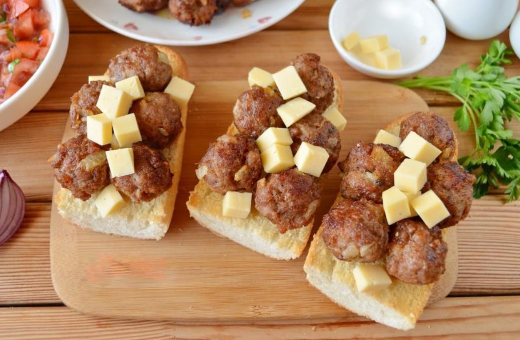 1. Этап. На булочки уложите мясные шарики и нарезанный кубиками твердый сыр. Поставьте сэндвичи в духовку чтобы сыр расплавился.