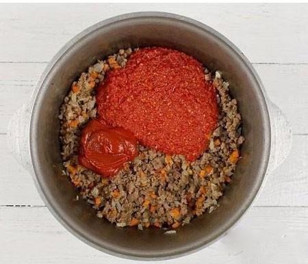 1. Этап. Смешайте фарш с морковью и луком, добавьте томатную пасту и натертые помидоры. Поставьте на медленный огонь и варите минут 15.