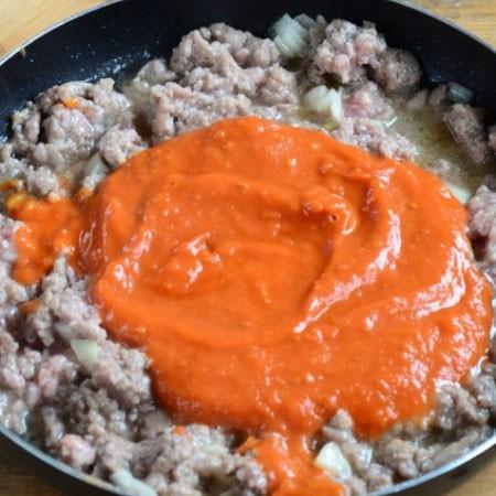 1. Этап. Добавьте к фаршу томатный соус, перемешайте и прогрейте несколько минут.