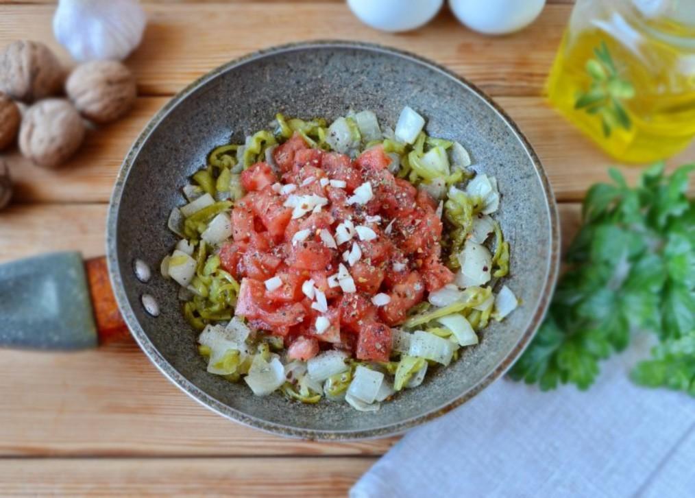 1. Этап. Добавьте в сковороду помидор без кожи и нарезанный кубиками, также измельченный чеснок, перец, соль и хмели-сунели. Тушите в течении нескольких минут.
