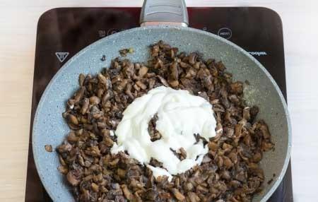 1. Этап. Добавьте к грибам несколько щепоток муки, пропущенный через пресс чеснок, перемешайте и готовьте минуту. После добавьте сметану, когда все закипит посолите и поперчите по вкусу, потушите на медленном огне еще минуту.