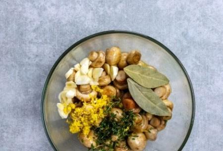 1. Этап. Грибы переложите в глубокую тарелку, добавьте сок и цедру лимона, лавровый лист, тимьян, чеснок, влейте остальное масло. Все хорошо перемешайте и посолите, поперчите по вкусу.