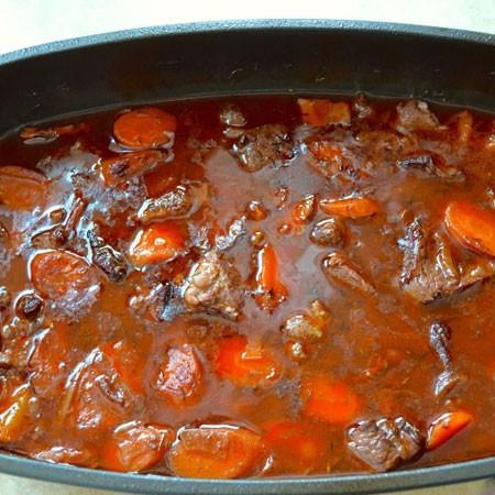 1. Этап. Добавьте лавровый лист, пропущенный через пресс чеснок и томатную пасту. Накройте крышкой и поставьте в духовку на 2,5 часа при 190 градусах.