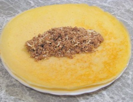1. Stage. Lay out the finished filling in the center of the pancake and fold it in an envelope.