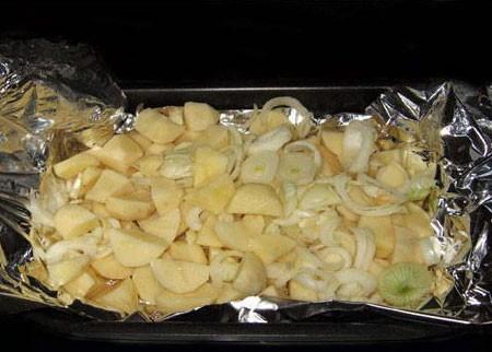 1. Этап. Картофель очистите и нарежьте дольками, выложите в форму для запекания застеленную фольгой и смазанную сливочным маслом, сверху выложите нарезанный кольцами лук.