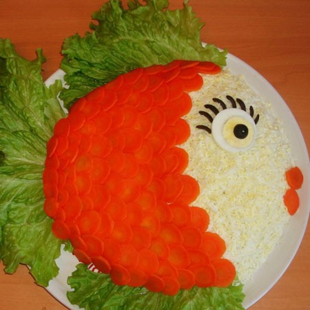 1. Stage. Grate the eggs on a fine grater and sprinkle part of the salad where the head will be. Cut the carrots into circles and put on a salad in the form of scales, also make an eye and a mouth. Put the finished salad in the refrigerator for 30 minutes to soak it.
