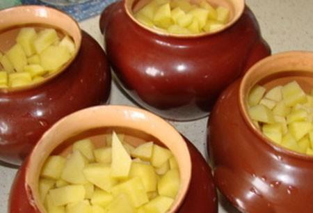 1. Этап. Картофель очистите, нарежьте кубиками. В горшочки выложите картофель.