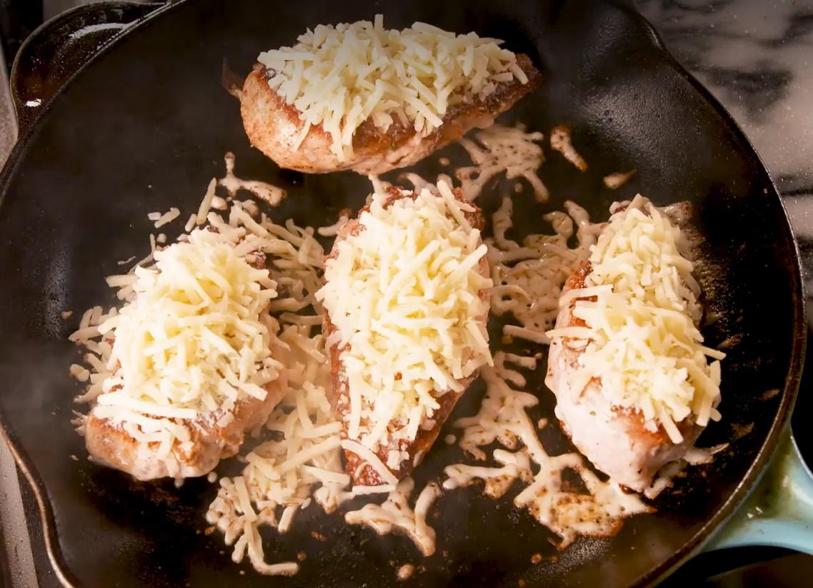 1. Этап. Уменьшите огонь до среднего, посыпьте курицу приправой и сверху выложите натертую моцареллу. Накройте сковороду крышкой и готовьте около 5 минут, пока сыр не расплавится и не начнет пузыриться.