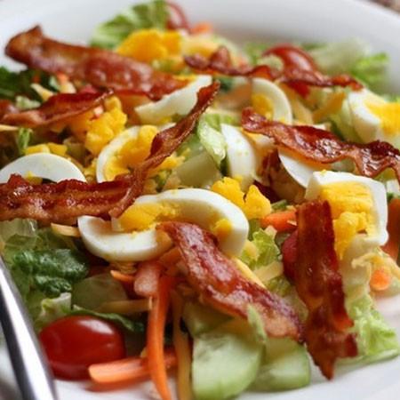 1. Этап. Положите в салатник салатные листья, добавьте зеленый лук, яйца, огурец и бекон. Перемешайте и заправьте салат с беконом и яйцами острым соусом.