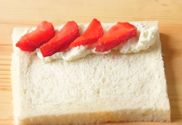 1. Этап. На край каждого кусочка хлеба положите творог, берите сладкий или же обычный по вашему вкусу, а также кусочки клубники или другие ягоды.