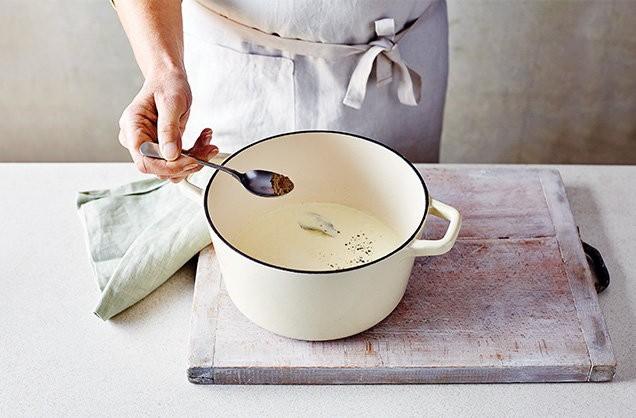 1. Этап. Вылейте молоко в большую кастрюлю, добавьте дольки чеснока и лавровый лист. Доведите до кипения, затем снимите с огня и добавьте мускатный орех и немного приправьте.