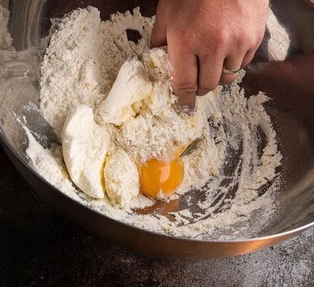 1. Этап. Муку просейте в миску, добавьте сыр, яйцо и мягкое сливочное масло, добавьте соль по вкусу и замесите эластичное тесто.