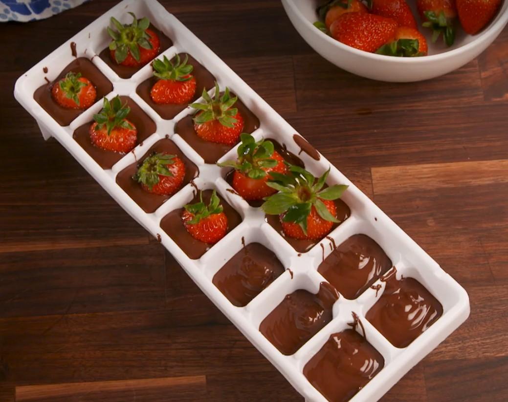 1. Этап. Выложите слой шоколадной смеси на дно каждой формы для кубиков льда, затем положите сверху по клубнике стеблем вверх. Выложите оставшуюся шоколадную смесь на клубнику.