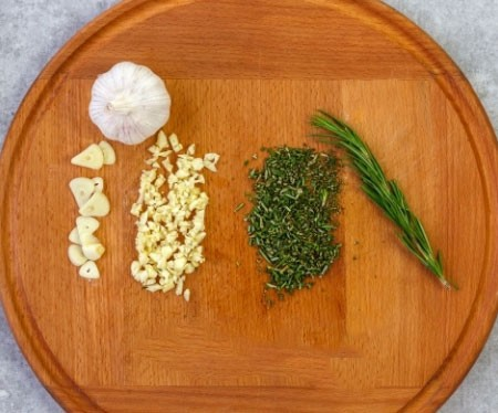 1. Stage. For rosemary, separate the leaves from the stick and cut the leaves. Cut one clove of garlic into slices, and pass the rest through a press or chop finely.