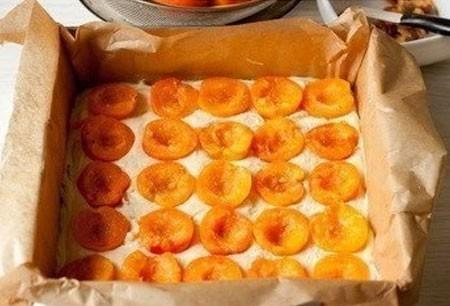 1. Этап. Выложите тесто в застеленную пергаментом форму, разровняйте и на верх положите половинки абрикоса. Если абрикос не сильно сладкий посыпьте немного сахаром.