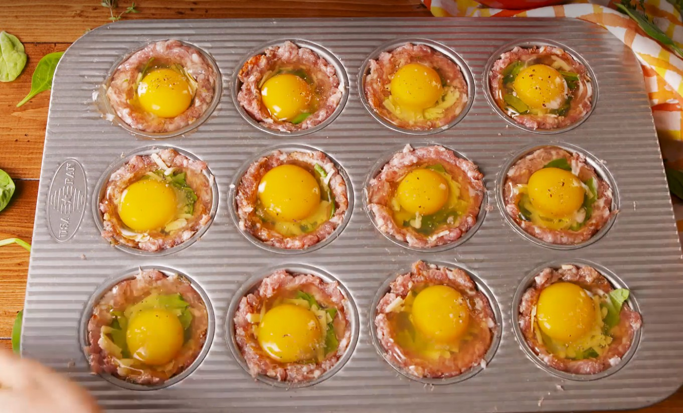1. Stage. Add a small handful of pork to each muffin tin well then press up the sides to create a cup. Divide spinach and cheese evenly between cups. Crack an egg on top of each cup and season with salt and pepper.