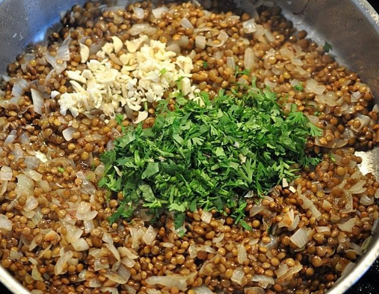 1. Этап. К чечевице добавьте измельченную зелень и оставшийся чеснок, готовьте в течении 5 минут.