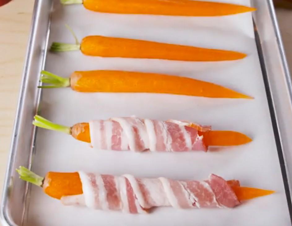 1. Этап. Разогрейте духовку до 200 С. Оберните каждую морковь полосой бекона и положите на большой противень. Смажьте все кленовым сиропом и приправьте черным перцем.