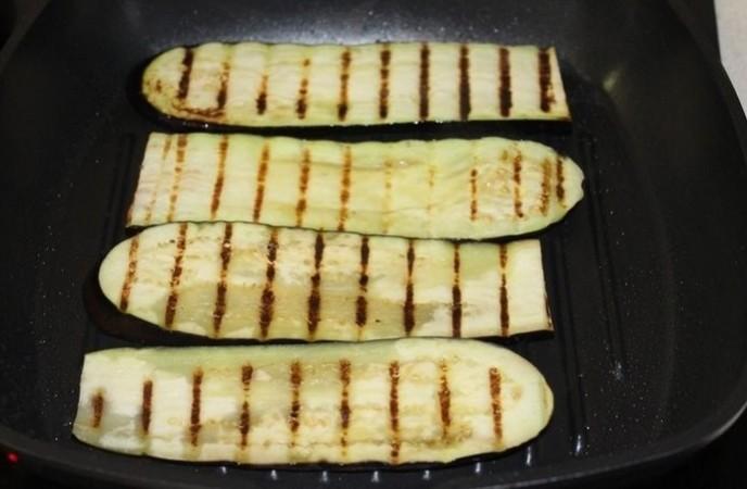1. Этап. На сковороде гриль разогрейте оливковое или подсолнечное масло. Обжарьте баклажаны с обеих сторон до мягкости примерно по 3 минуты с каждой стороны.