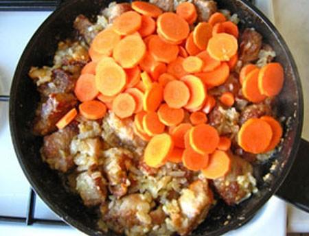 1. Этап. Затем к мясу добавьте мелко нарезанный лук и нарезанный кружочками морковь. Готовьте около 15 минут периодически помешивая.