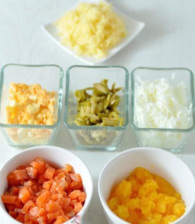 1. Этап. Яйца очистите от скорлупы, разделите на белки и желтки, отдельно натрите на мелкой терке. Семгу нарежьте кубиками, апельсин очистите от всех жилок и пленочки - нарежьте кубиками. Сыр натрите на мелкой терке. Оливки нарежьте соломкой.