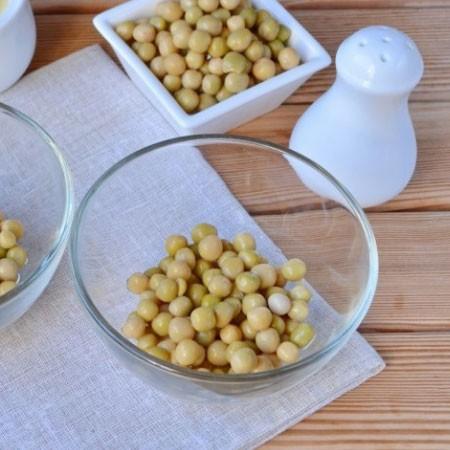 1. Этап. Начнем собирать салат. Первым слоем распределите по креманкам по 2 ст. л. консервированного горошка.