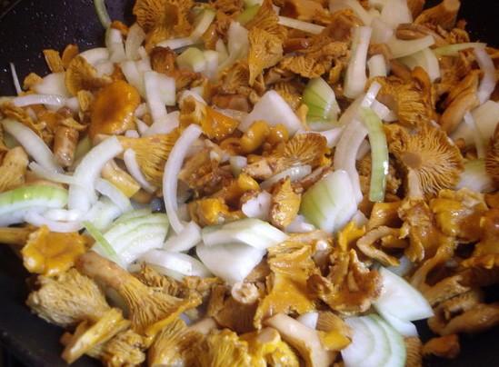 1. Этап. Лук нарежьте полукольцами и обжарьте с лисичками на половине растительного масла, добавьте перец чили. Готовьте пока не уйдет влага от грибов.